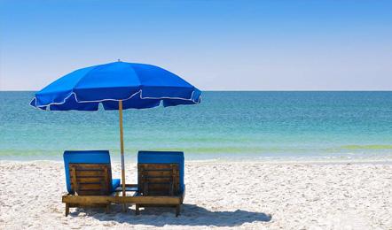 Serviceleistungen im Hotel: Sonnenliege und -schirm am Strand